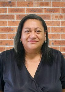 Photo of Heather Latu, wearing black shirt and standing in front of brick wall.