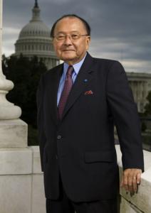 Photo of Sen. Daniel Inouye, standing in front of US Capitol building, wearing black suit and red tie.