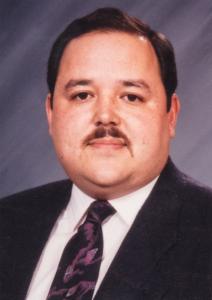 Photo of Glenn Yamahiro, wearing a black suit and tie.