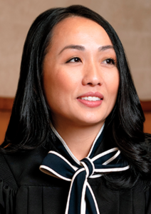 Photo of Kashoua Kristy Yang, wearing a black blouse with a bow at the neck.